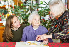 Elderly home care. Photo of elderly women having breakfast with her caregivers royalty free stock photo