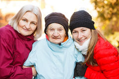 Elderly home care. Photo of elderly women and her carers royalty free stock images