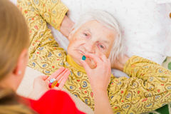 Elderly home care. Photo of elderly women taking the medication royalty free stock image