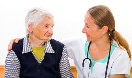 Elderly home care. Photo of elderly women with the young doctor stock image
