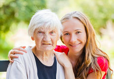 Elderly home care. Portrait of elderly women and her grandchild royalty free stock photo
