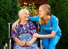 Elderly Home Care. Supporting young doctor with elderly patient at the nursing home stock photo