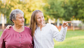 Elderly home care. Elderly women with her caretaker in the nature stock photo