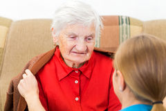 Elderly home care. Young carer wrap the elderly women with warm sweater stock image