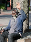 Elderly homeless man waving Royalty Free Stock Photography