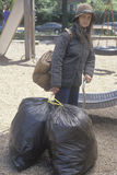 Elderly homeless woman holding possessions in garbage bags, Chicago, Illinois Stock Photos
