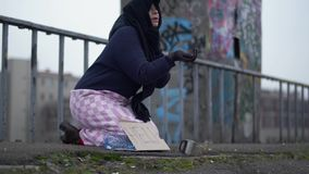 Adult homeless woman with outstretched hand sits on the bridge in cold windy grey weather asking for alms and help and. Elderly homeless woman with outstretched stock video footage