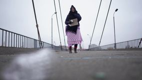 Adult homeless woman stay on the bridge near the river port in cold windy grey weather asking for help and begging money. Elderly homeless woman stay on the stock video footage