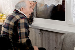 Elderly horrified man watching through a window Stock Images