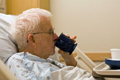 Elderly hospital patient drinking coffee stock photography