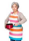 Elderly housewife holding with saucepan Royalty Free Stock Photo