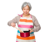 Elderly housewife use of saucepan Royalty Free Stock Photography