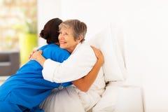 Elderly hugging caregiver. Happy elderly women hugging caregiver on bed Royalty Free Stock Image