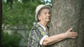 Elderly hugging tree trunk her hands in the forest. Elderly mature woman aged 80s dressed in white hat hugging tree trunk her hands in the forest. Woman is stock video footage