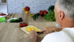 Elderly husband cutting vegetables, cooking dinner at home, health care, hobby. Stock photo royalty free stock photo
