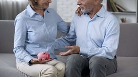 Elderly husband and wife on couch holding piggy bank, reliable deposit, banking stock image