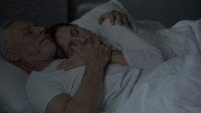Elderly husband and wife sleeping in bed, woman put head on man chest, loving