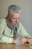 Elderly ill man with pills Stock Images