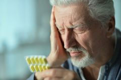 Elderly ill man with pills in hand Royalty Free Stock Photography