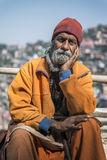 Elderly Indian beard man, hand on cheek, look front, wearing cultural rope and beads with walking stick. Stock Image