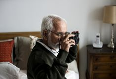 An elderly Indian man at the retirement house taking a photo Stock Image