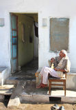 Elderly Indian man sits outside his home Stock Photos