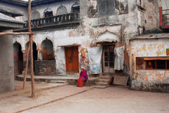 Elderly Indian woman sits alone inside the yard royalty free stock photography