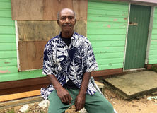 Elderly indigenous Fijian man. In her 70`s sit outside his village home. Real people copy space stock images