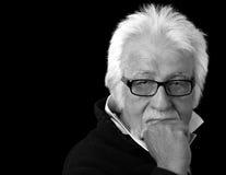 Elderly intelligent man on black. Portrait of an elderly intelligent man on a black background Stock Images
