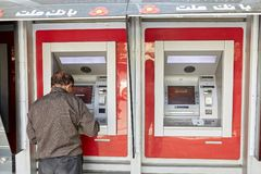 Elderly iranian man withdraws money from an ATM machine, Yazd. Stock Photos