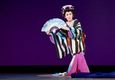 Elderly Japanese Festival Dancer. Kagoshima City, Japan, October 27, 2007. An elderly senior Japanese dancer in kimono perform with a fan onstage in the night royalty free stock image