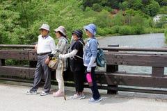 June 2018, Elderly Japanese hikers bridge river mountains Alps, Kamikochi, Japan