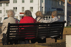 Elderly ladies on a bench. Four elderly ladies chatting on a bench Stock Image