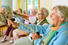 Elderly ladies exercising in a gym. Large group of happy enthusiastic elderly ladies exercising in a gym sitting in chairs doing stretching exercises with rubber Royalty Free Stock Image