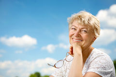 The elderly lady. The beautiful woman is elderly against the bright blue sky royalty free stock image