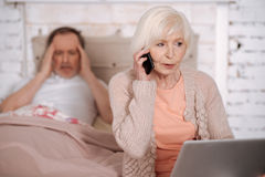 Elderly lady calling emergency for ill husband. Hurry up. Senior women calling emergency while sitting on bed holding laptop near her ill husband with terrible Royalty Free Stock Images