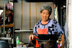 Elderly lady cooking at her food stall Royalty Free Stock Photo