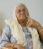 An elderly lady in deep thought Stock Photography