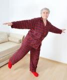 Elderly lady doing gymnastics. Elderly lady in pajamas doing gymnastics Stock Image