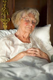 Elderly lady dozing in her bed. Elderly lady sitting propped up against the pillows in her nightgown and glasses dozing in her bed stock image