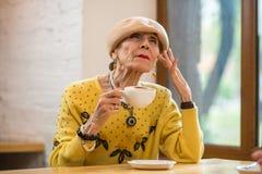 Elderly lady drinking coffee. Stock Photos