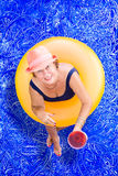 Elderly lady drinking pina colada in the pool Stock Image