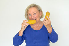Elderly lady enjoying fresh corn on the cob Royalty Free Stock Image