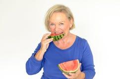 Elderly lady enjoying fresh watermelon Stock Photos