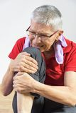 Elderly lady experiencing knee pain. Senior elderly lady having a bad pain in her knee after a tough workout routine Stock Images