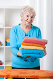 Elderly lady folding towels Royalty Free Stock Photos