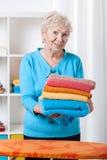 Elderly lady folding towels Royalty Free Stock Photos