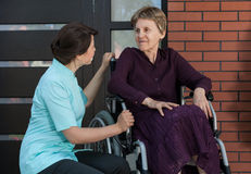 Elderly lady in front of house. Nurse and elderly lady in front of house royalty free stock images
