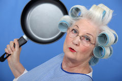 Elderly lady with frying pan Royalty Free Stock Photography