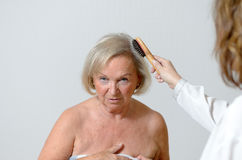 Elderly lady gets her hair combed Stock Photos